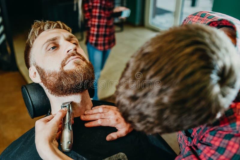 Il barbiere taglia la sua barba ad un uomo nel salone fotografia stock libera da diritti