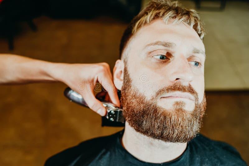Il barbiere taglia la sua barba ad un uomo nel salone fotografie stock libere da diritti