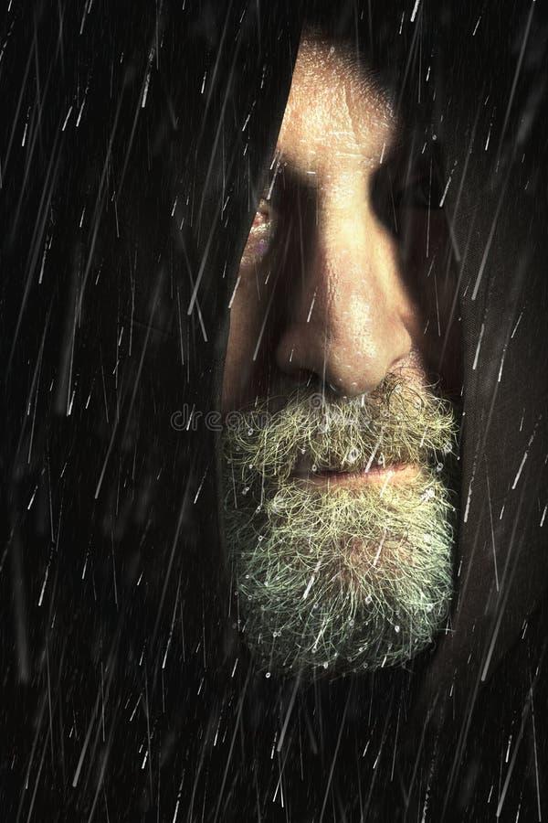 Il barbone incappucciato dell'uomo nella pioggia con tela di sacco e la barba, affronta parzialmente nascosto immagine stock