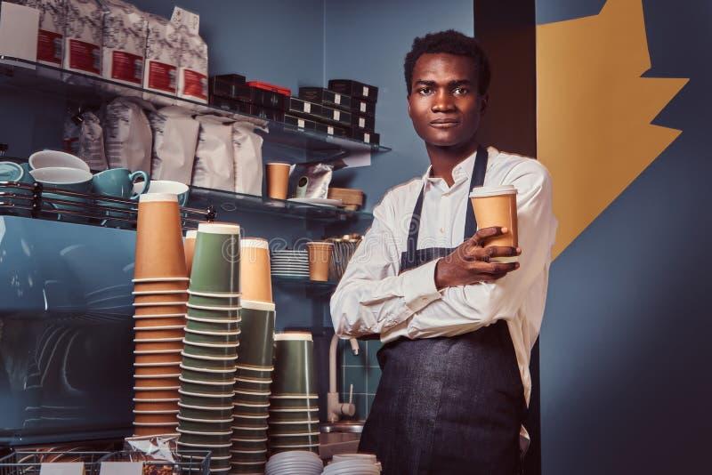 Il barista afroamericano bello in uniforme tiene una tazza di caffè mentre sta nella sua caffetteria immagini stock