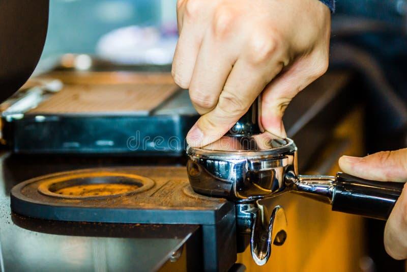 Il barista comprime sul portafilter in una caffetteria fotografia stock libera da diritti