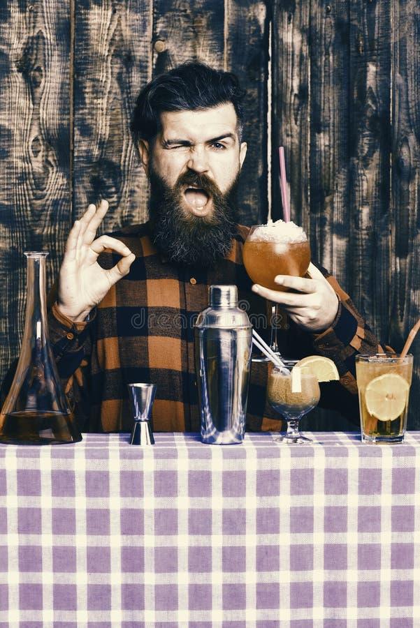 Il barista con la barba ed il fronte di lampeggiamento tiene il vetro con il cocktail della cannuccia L'uomo mostra il gesto gius fotografia stock libera da diritti