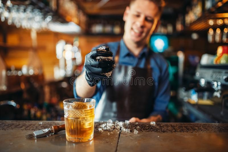 Il barista maschio lavora con ghiaccio al contatore della barra fotografie stock