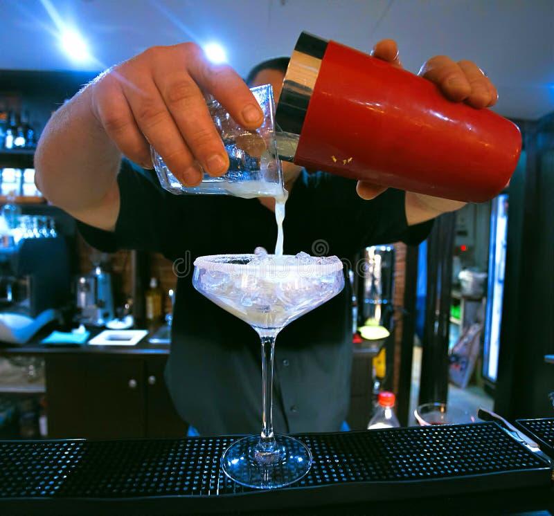 Il barista mescola il cocktail Ha versato una bevanda da un agitatore rosso in un vetro con ghiaccio immagini stock