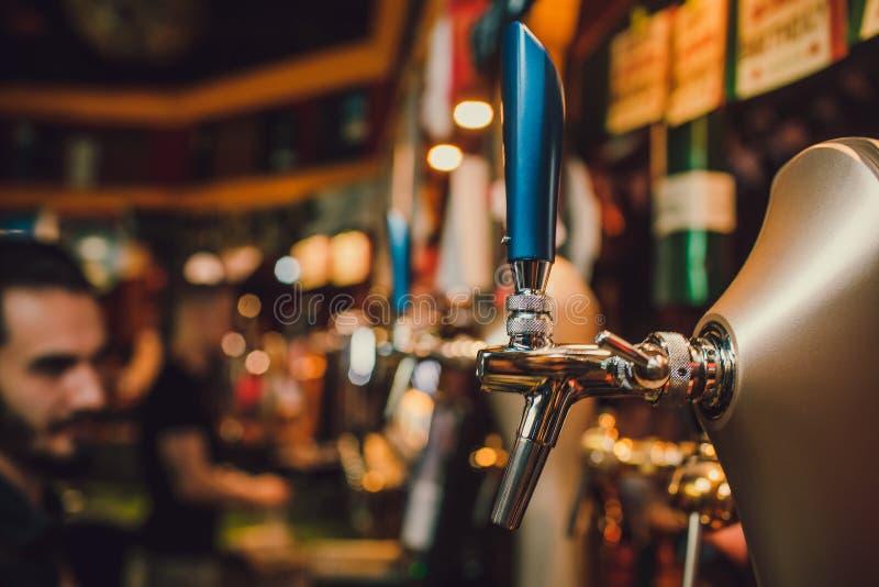 Il barista passa il versamento della birra chiara in un vetro immagine stock libera da diritti