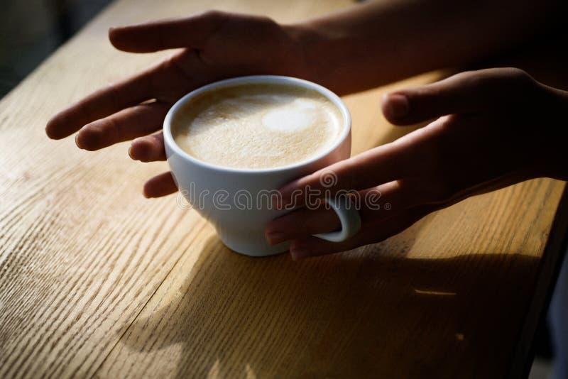 Il barista propone la tazza di caffè del caffè espresso o di americano il caffè fresco di mattina con latte e la crema schiumano  immagini stock