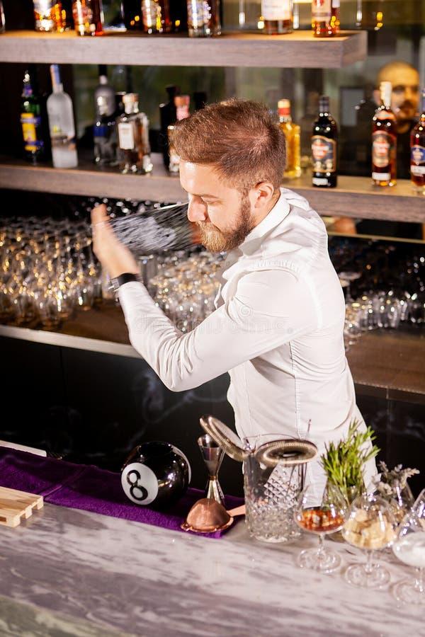 Il barista sta facendo il cocktail al contatore della barra fotografie stock