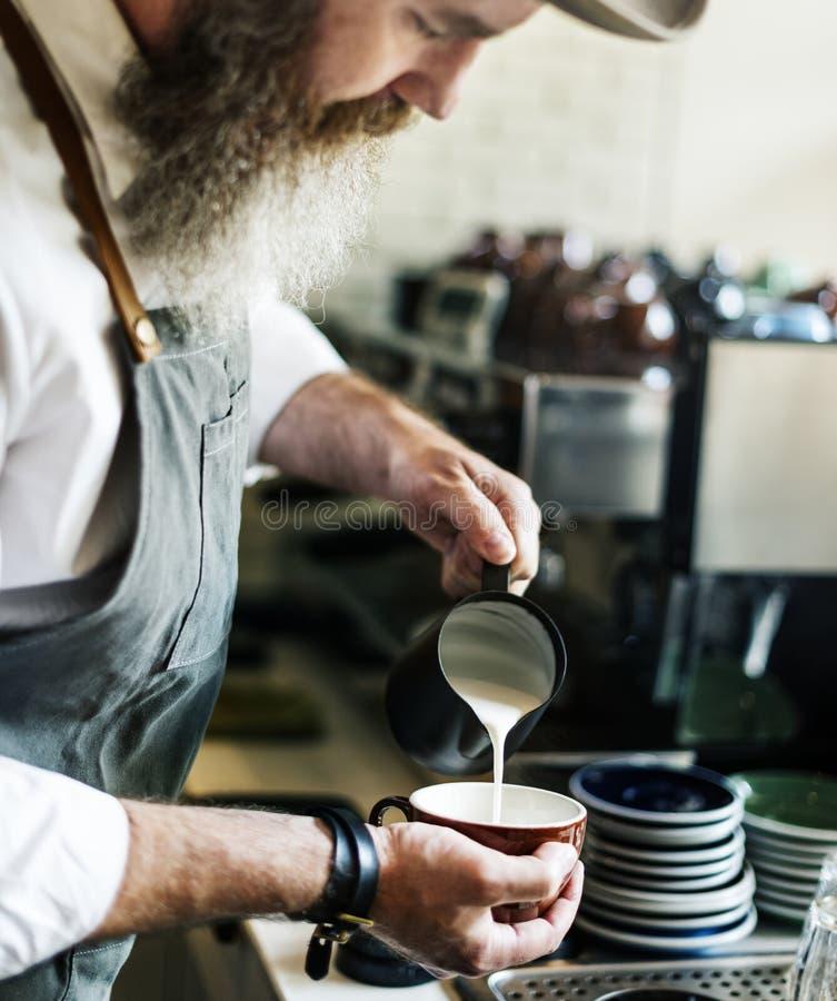 Il barista sta producendo il caffè fotografia stock