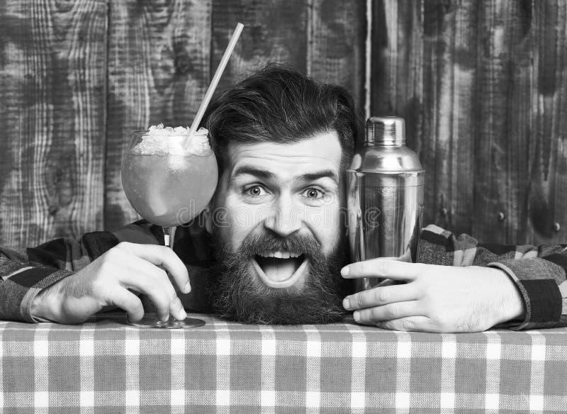 Il barista tiene il cocktail con ghiaccio e paglia Il barista con la barba ed il fronte felice ha messo la testa sulla tovaglia fotografie stock libere da diritti