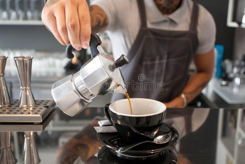 Il barista versa il caffè dalla caffettiera dentro il caffè contemporaneo di stile di progettazione con la barra fotografia stock