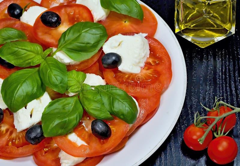 Il basilico della mozzarella del pomodoro lascia le olive nere e l'olio d'oliva sulla tavola di legno immagine stock