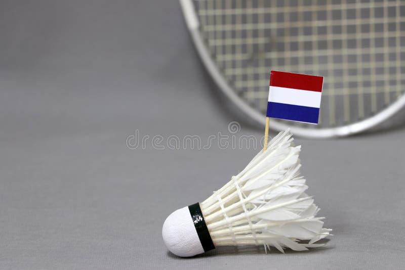 Il bastone della bandiera di Mini Netherlands sul volano bianco sui precedenti grigi e fuori mette a fuoco la racchetta di volano immagini stock libere da diritti