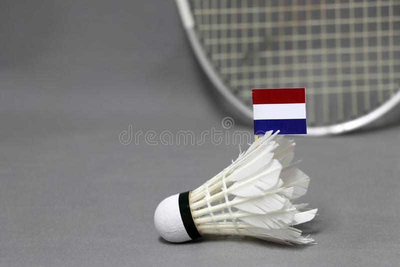 Il bastone della bandiera di Mini Netherlands sul volano bianco sui precedenti grigi e fuori mette a fuoco la racchetta di volano fotografia stock libera da diritti
