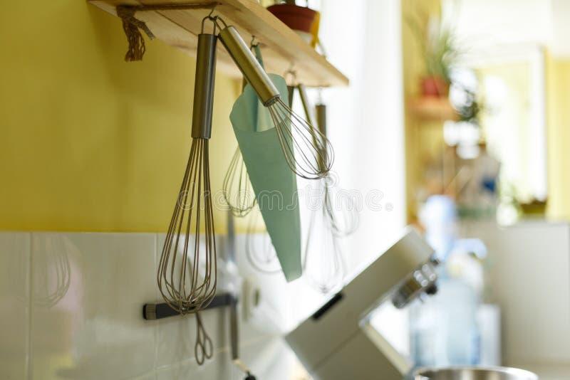 Il battitore sbatte, borsa del ` s del confettiere ed altri accessori della cucina appendono sulla parete gialla della cucina fotografia stock libera da diritti