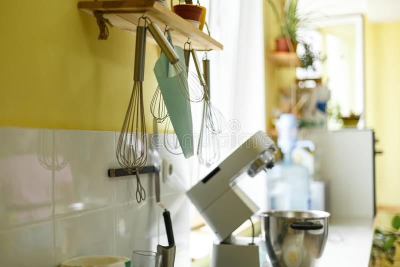 Il battitore sbatte, borsa del ` s del confettiere ed altri accessori della cucina appendono sulla parete gialla della cucina immagine stock