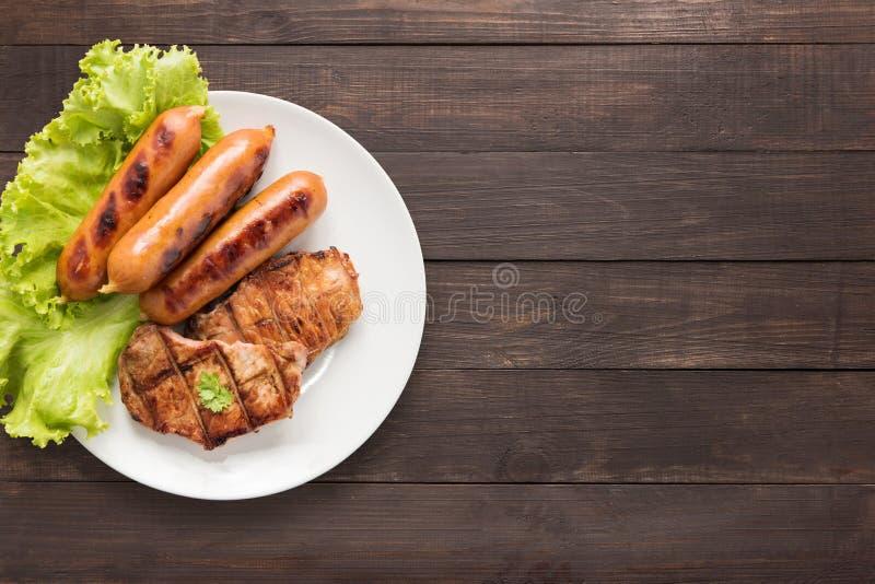 Il BBQ di vista superiore ha grigliato la carne, le salsiccie e le verdure sul piatto sul wo fotografia stock