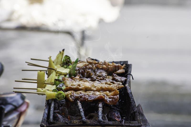 Il BBQ ha grigliato la carne con le verdure e le salse al pomodoro sulle griglie d'acciaio con il calore fotografia stock