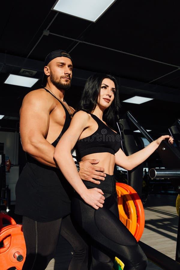 Il bei giovani uomo e girll sexy sportivi delle coppie posano la condizione nella palestra fotografia stock libera da diritti
