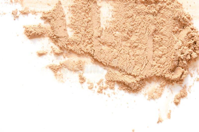 Il beige ha schiantato la cipria per trucco come campione del prodotto cosmetico, isolato su fondo bianco immagini stock
