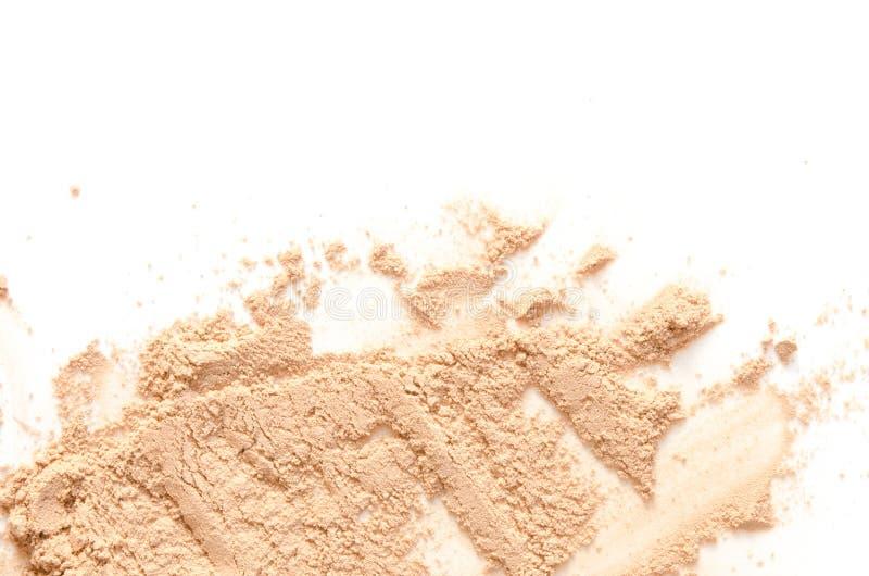 Il beige ha schiantato la cipria per trucco come campione del prodotto cosmetico, isolato su fondo bianco immagini stock libere da diritti