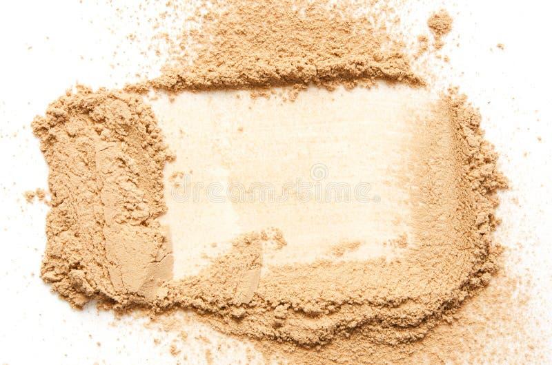 Il beige ha schiantato la cipria per trucco come campione del prodotto cosmetico, isolato su fondo bianco fotografie stock