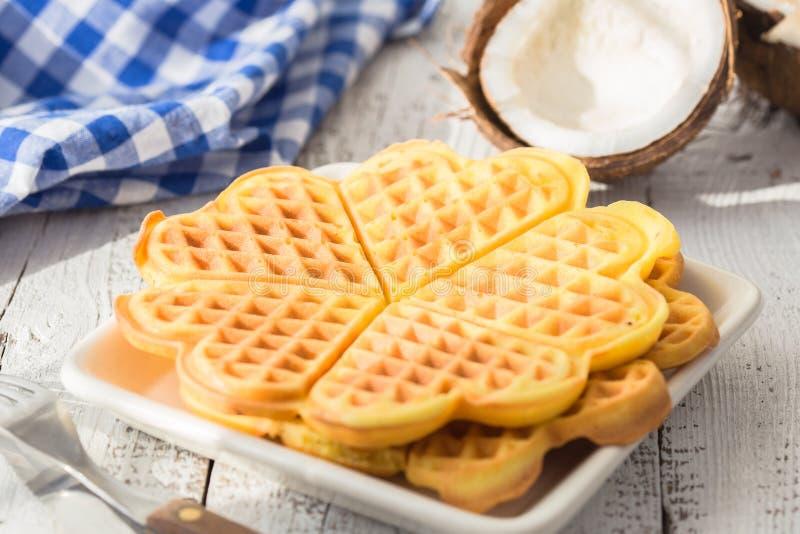 Il Belgio waffles con i lamponi della salsa su fondo di legno Il Belgio dolce waffles herts Cialde del Belgio della noce di cocco immagine stock libera da diritti