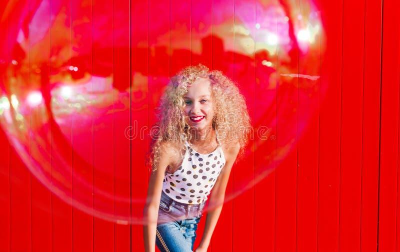Il bello adolescente gonfia le bolle di sapone contro la parete rossa fotografie stock