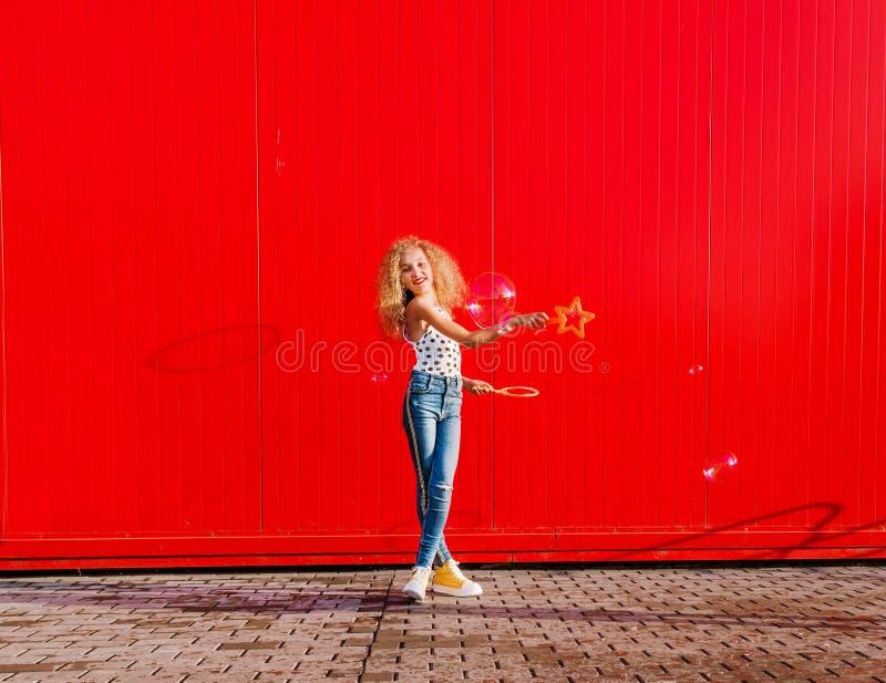 Il bello adolescente gonfia le bolle di sapone contro la parete rossa immagine stock libera da diritti
