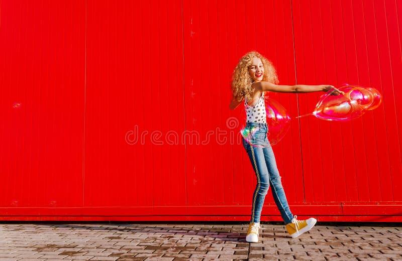 Il bello adolescente gonfia le bolle di sapone contro la parete rossa fotografia stock