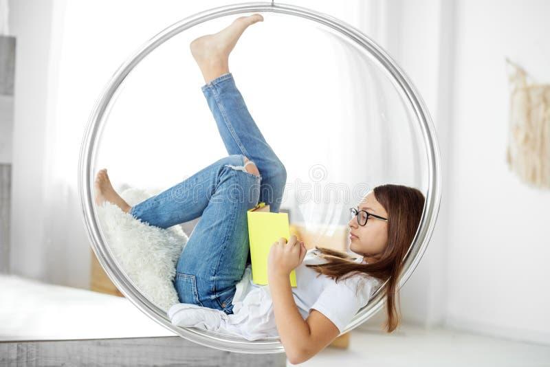 Il bello adolescente sta leggendo un libro nella stanza Concetto di istruzione, dell'hobby, dello studio e del giorno del libro d immagini stock libere da diritti