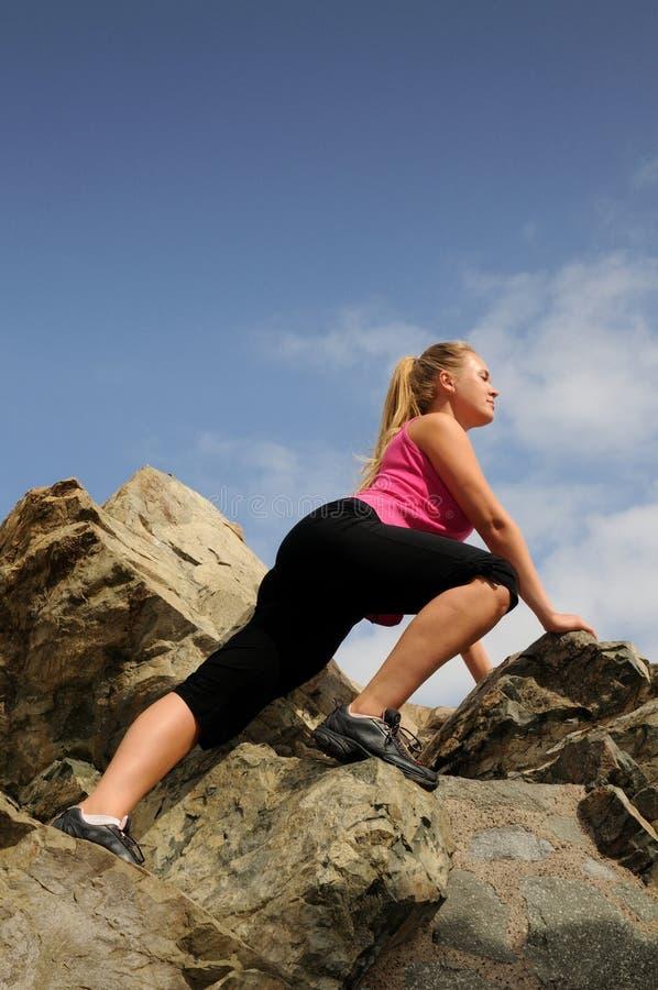 Il bello alpinista della donna sta arrampicandosi su una montagna immagini stock