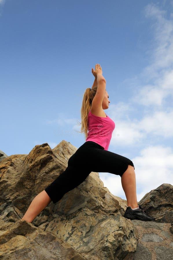 Il bello alpinista della donna sta arrampicandosi su una montagna fotografia stock