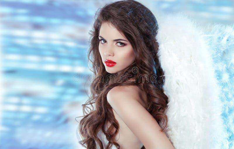 Il bello angelo castana della ragazza sopra il partito di discoteca accende il fondo immagine stock