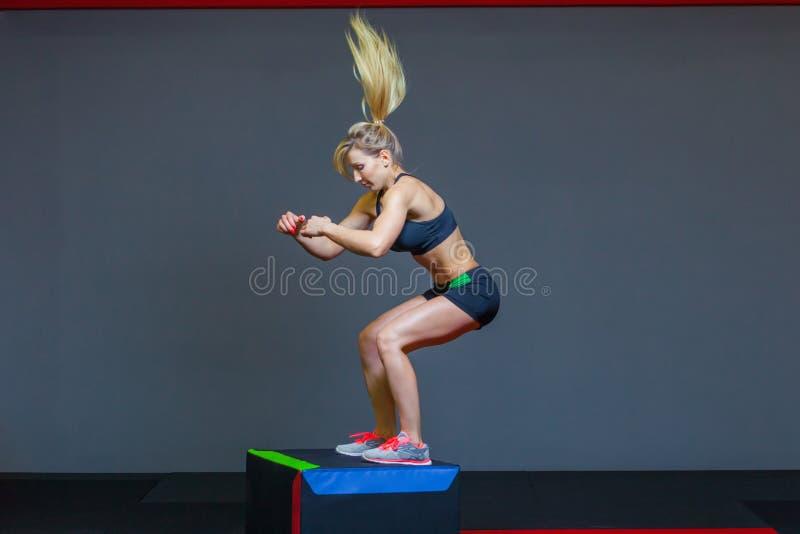 Il bello atleta femminile di forma fisica esegue i salti della scatola in una palestra scura che porta la cima nera di sport e le immagini stock