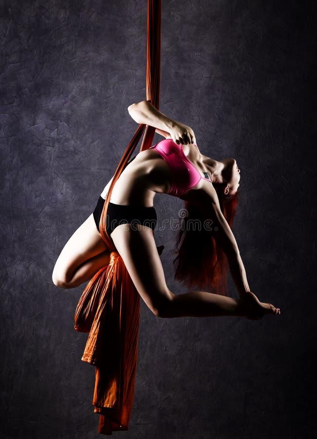 Il bello ballerino sexy su seta aerea, la distorsione graziosa, acrobata esegue un trucco sull'nastri fotografia stock