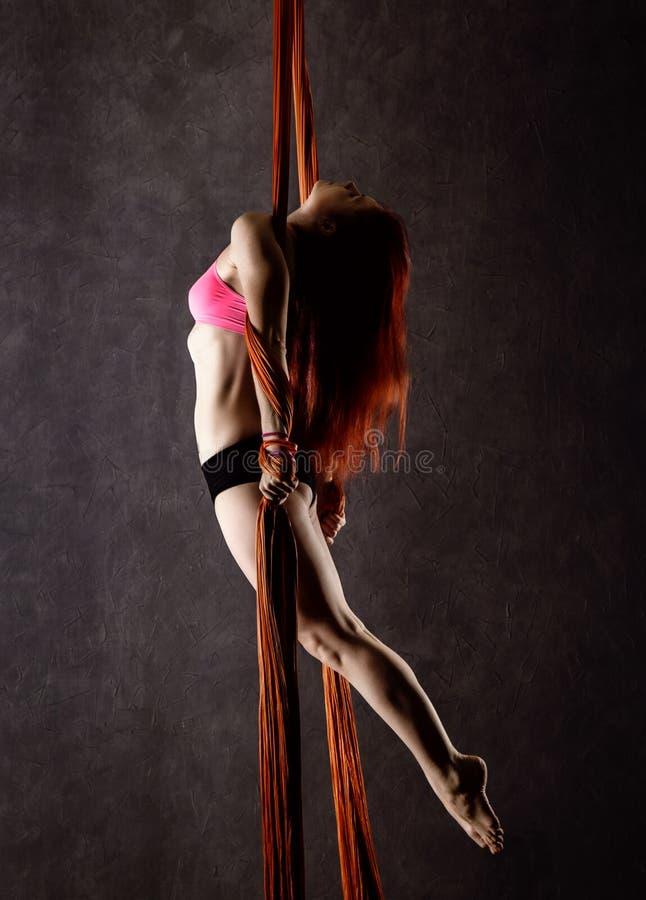 Il bello ballerino sexy su seta aerea, la distorsione graziosa, acrobata esegue un trucco sull'nastri immagine stock