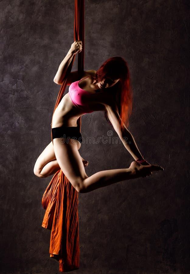 Il bello ballerino sexy su seta aerea, la distorsione graziosa, acrobata esegue un trucco sull'nastri fotografia stock libera da diritti
