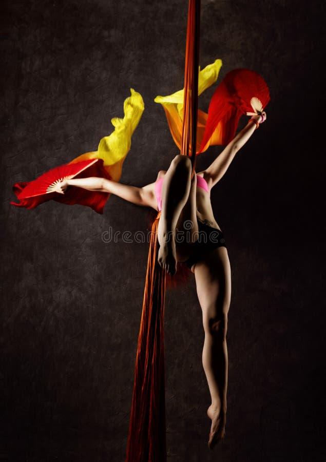 Il bello ballerino sexy su seta aerea, la distorsione graziosa, acrobata esegue un trucco sull'nastri fotografie stock