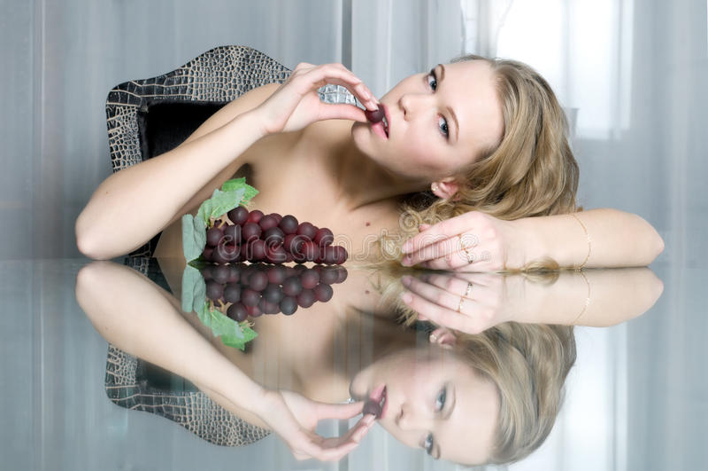 Il bello blonde sta mangiando l'uva fotografia stock libera da diritti