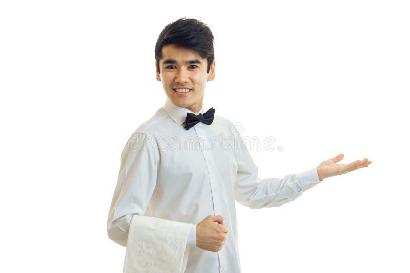 Il bello cameriere affascinante in una camicia bianca sorride e dà la sua mano verso fotografia stock