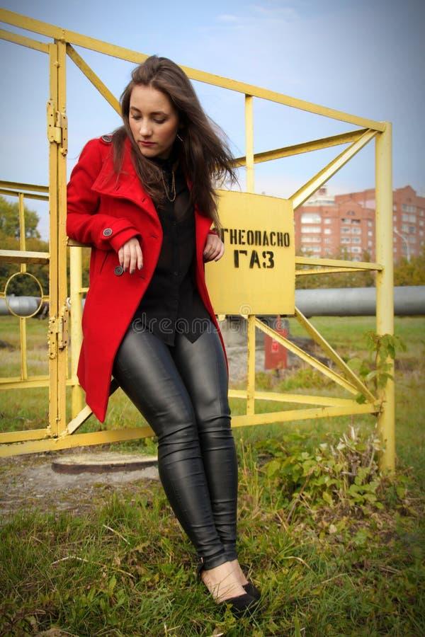 Download Il Bello Cappotto Della Ragazza In Rosso è Basato Sul Recinto Fotografia Stock - Immagine di people, basato: 56890518