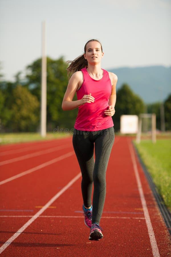 Il bello corridore della giovane donna funziona su una pista nel afte dell'inizio dell'estate immagini stock