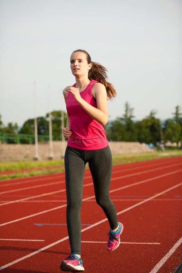 Il bello corridore della giovane donna funziona su una pista nel afte dell'inizio dell'estate immagine stock