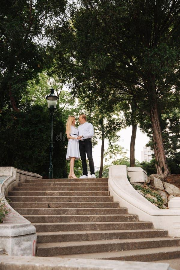 Il bello cuple sta sulle scale e si abbraccia Uomo e donna che camminano nel parco Storia di amore immagini stock libere da diritti