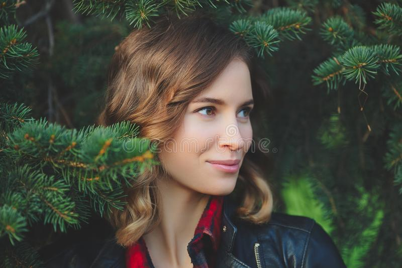 Il bello fronte di una giovane donna sorridente contro un fondo di abete si ramifica immagini stock