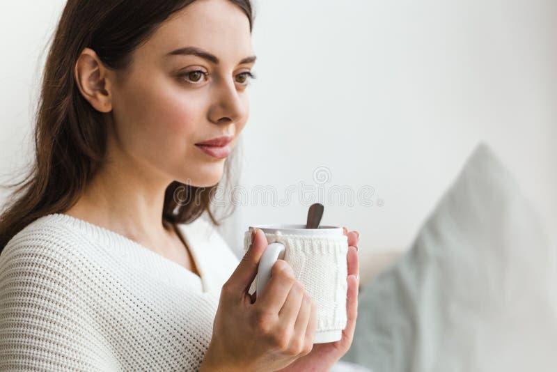 Il bello fronte di una ragazza, una ragazza in maglione bianco si siede su un sofà con una tazza di tè caldo in sue mani fotografie stock