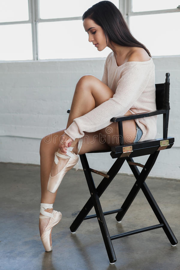 Il bello giovane ballerino merletta le scarpe del pointe fotografia stock libera da diritti