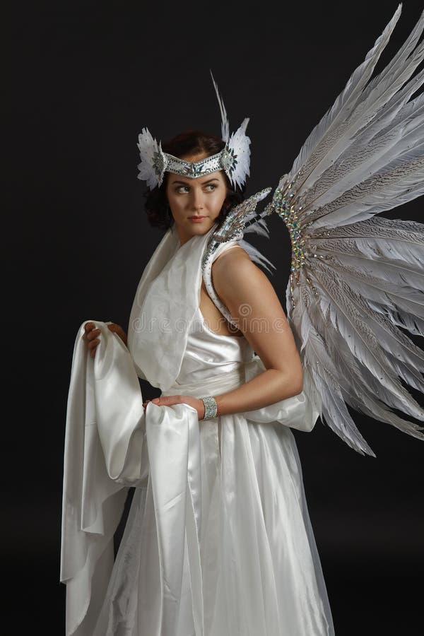 Il bello giovane modello che porta un vestito bianco con l'angelo traversa dentro fotografia stock libera da diritti