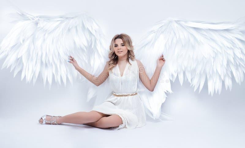 Il bello giovane modello con l'angelo aperto traversa la seduta volando nello studio immagini stock libere da diritti