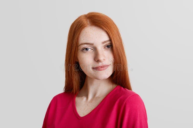 Il bello giovane modello femminile freckled serio, ha lentiggini sul fronte, lungamente capelli rossi diritti, vestiti con indiff fotografia stock libera da diritti